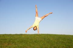 Young woman cartwheels Stock Photos