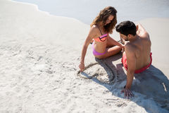 Young woman carving heart shape in sand while sitting with boyfriend at beach Stock Photos