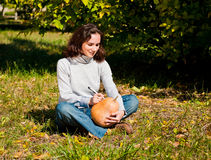 Young woman carving a pumpkin for Halloween Royalty Free Stock Image