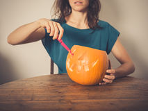 Young woman carving a pumpkin lantern Stock Photo