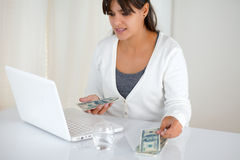 Young woman with cash money buying on the internet. Portrait of a young woman with cash money while is buying on the internet with her laptop computer Royalty Free Stock Photo