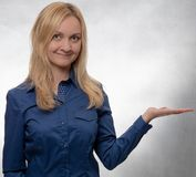 Young woman in casual blue shirt with open hand looking straight into camera stock images