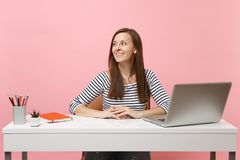 Young woman in casual clothes looking aside sit, work at white desk with contemporary pc laptop isolated on pastel pink