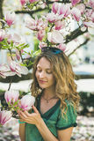 Young woman in casual clothes touching magnolia flowers Royalty Free Stock Photo