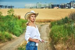 Young woman in casual clothes for a walk in a field of wheat. A woman in a stylish hat Royalty Free Stock Images