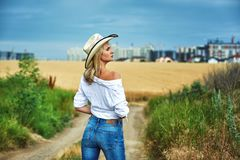 Young woman in casual clothes for a walk in a field of wheat. A woman in a stylish hat Stock Photography