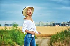 Young woman in casual clothes for a walk in a field of wheat. A woman in a stylish hat Stock Images