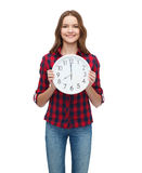 Young woman in casual clothes with wall clock Royalty Free Stock Images