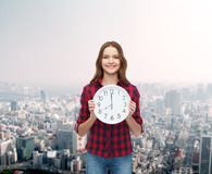 Young woman in casual clothes with wall clock Royalty Free Stock Photo
