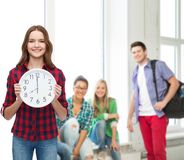 Young woman in casual clothes with wall clock Stock Photography