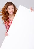 Young woman in casual clothing holding empty board Stock Image