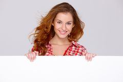 Young woman in casual clothing holding empty board Royalty Free Stock Photography