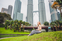 A young woman in casual dress using laptop in a tropical park on the background of skyscrapers. Mobile Office concept.  Stock Image