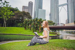 A young woman in casual dress using laptop in a tropical park on the background of skyscrapers. Mobile Office concept Royalty Free Stock Photos