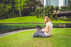 A young woman in casual dress using laptop in a tropical park on the background of skyscrapers. Mobile Office concept.  Royalty Free Stock Image