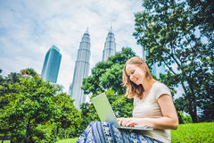 A young woman in casual dress using laptop in a tropical park on the background of skyscrapers. Mobile Office concept.  Royalty Free Stock Photo