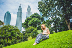 A young woman in casual dress using laptop in a tropical park on the background of skyscrapers. Mobile Office concept.  Royalty Free Stock Images