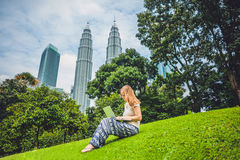 A young woman in casual dress using laptop in a tropical park on the background of skyscrapers. Mobile Office concept.  Royalty Free Stock Photography