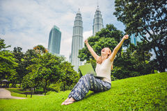 A young woman in casual dress using laptop in a tropical park on the background of skyscrapers. Mobile Office concept Stock Image