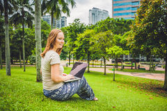 A young woman in casual dress using laptop in a tropical park on the background of skyscrapers. Mobile Office concept Royalty Free Stock Image