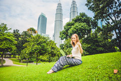 A young woman in casual dress using laptop in a tropical park on the background of skyscrapers. Mobile Office concept Royalty Free Stock Photo
