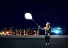 Young woman in casual holding balloon Stock Photo
