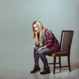 Young woman in casual outfit sitting on chair Stock Photos