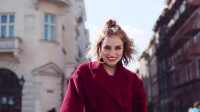 Young woman in a casual red coat playfully touching her hair, laughing towards the camera, smiling jocosely. Old city stock video footage