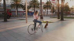 Pretty girl on her urban vintage bicycle at sunset. Young woman in casual trendy hipster outfit on bicycle, stopped on sidewalk to talk to friends on messaging stock video