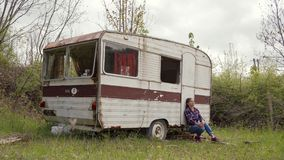 Young woman in casual wear meditatively sits near abandoned old caravan. 4k stock video