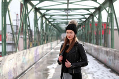 Young woman in casual winter clothes. Beautiful girl on a bridge in a European city Stock Images