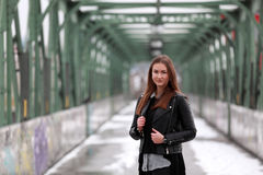 Young woman in casual winter clothes. Beautiful girl on a bridge in a European city stock image