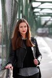 Young woman in casual winter clothes. Beautiful girl on a bridge in a European city royalty free stock images