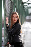 Young woman in casual winter clothes. Beautiful girl on a bridge in a European city royalty free stock photography