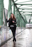 Young woman in casual winter clothes. Beautiful girl on a bridge in a European city Royalty Free Stock Photos