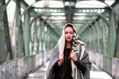 Young woman in casual winter clothes. Beautiful girl on a bridge in a European city royalty free stock photo