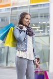 Young woman in casuals carrying shopping bags outdoors Royalty Free Stock Photography