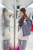 Young woman in casuals window shopping Stock Images