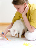 Young woman and cat. Drawing together sitting on the floor stock images
