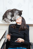 Young woman and cat buy things online with credit card and smart phone Royalty Free Stock Photography