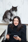 Young woman and cat buy things online with credit card and smart phone Stock Photography