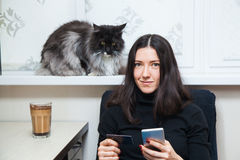 Young woman and cat buy things online with credit card and smart phone Stock Photo