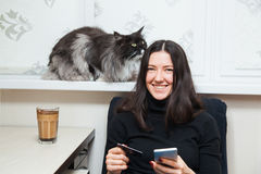 Young woman and cat buy things online with credit card and smart phone Royalty Free Stock Images