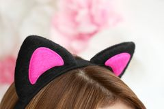 Young woman in cat ears on blurred background. Closeup Royalty Free Stock Image