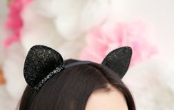 Young woman in cat ears on blurred background. Closeup Stock Images