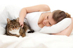 Young woman with cat elaxing in white bedding Stock Image