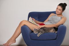Young woman with cat and magazine on armchair at home royalty free stock photos