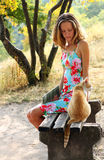 Young woman and a cat sitting on the bench Stock Photos