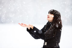 Young woman catches snowflakes Stock Photos