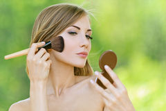 Young woman causes powder to face. Portrait of beautiful young woman causes powder to face, against green of summer park Stock Image